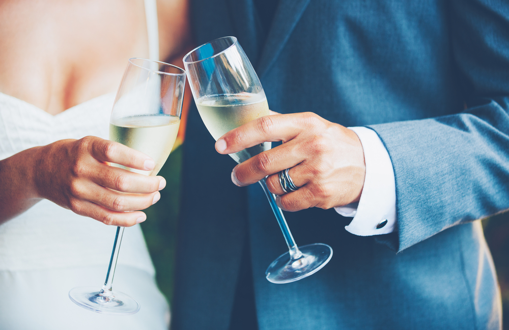 Wedding Couple Raising A Glass Of Champagne Each