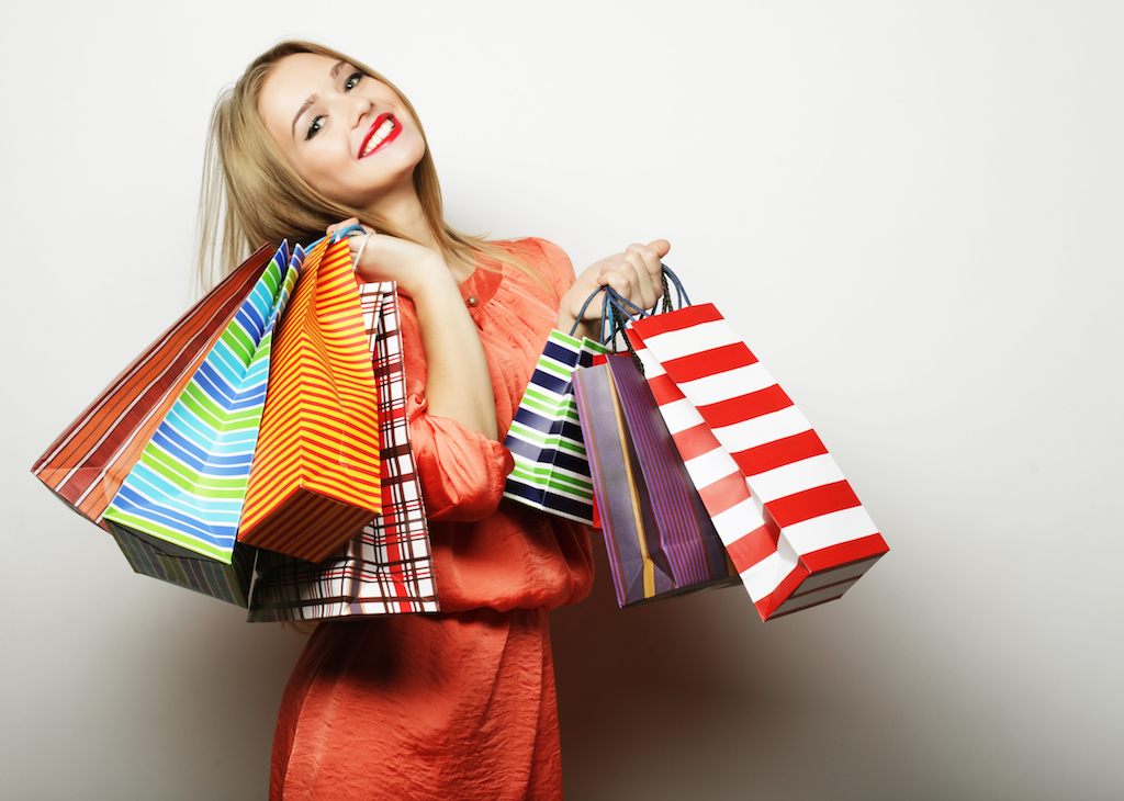 Smiling woman holding multiple shopping bags