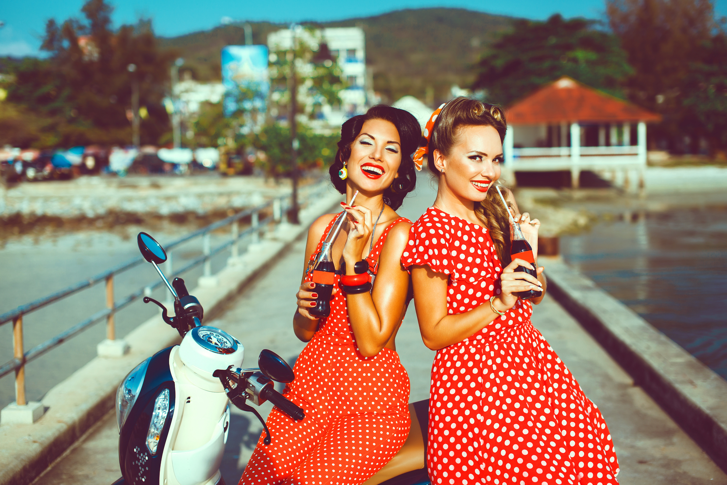 Two smiling women in pin-up attire drinking cola